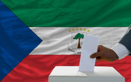 man putting ballot in a box during elections  in front of national flag of equatorial guinea photo
