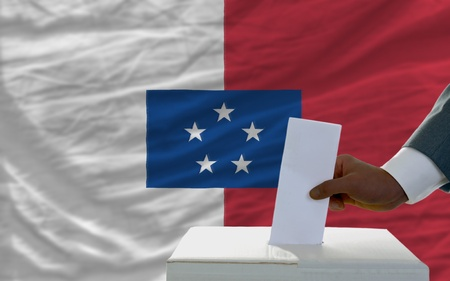 man putting ballot in a box during elections  in front of national flag of franceville Stock Photo - 12063229