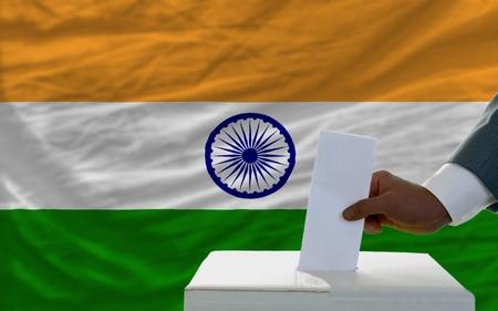 democracia: el hombre poniendo voto en una urna durante las elecciones al frente de la bandera nacional de la India