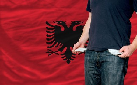 poor man showing empty pockets in front of albania flag photo