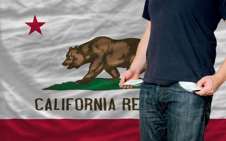 poor man showing empty pockets in front of california flag Stock Photo