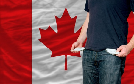 money in pocket: poor man showing empty pockets in front of canada flag