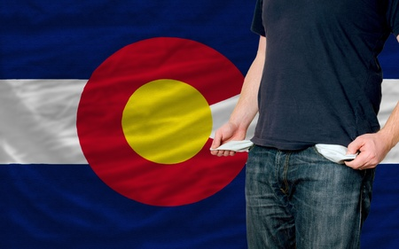 poor man showing empty pockets in front of colorado flag photo