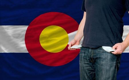 colorado flag: poor man showing empty pockets in front of colorado flag