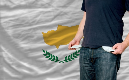 poor man showing empty pockets in front of cyprus flag
