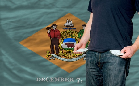 poor man showing empty pockets in front of delaware flag
