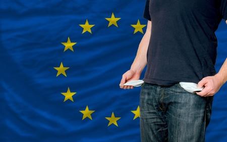 hombre pobre: pobre hombre mostrando los bolsillos vac�os frente a la bandera de Europa Foto de archivo