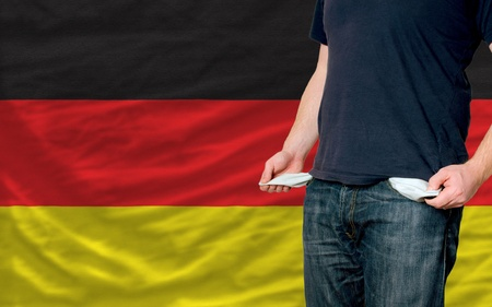 poor man showing empty pockets in front of germany flag