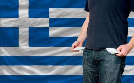 poor man showing empty pockets in front of greece flag