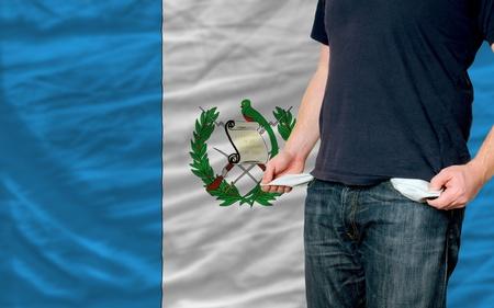 bandera de guatemala: pobre hombre mostrando los bolsillos vac�os frente a Guatemala Bandera Foto de archivo