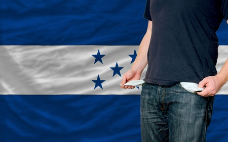 poor man showing empty pockets in front of honduras flag photo