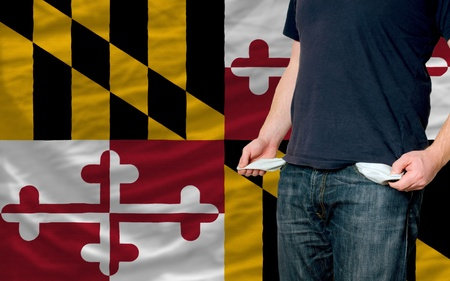 maryland flag: poor man showing empty pockets in front of american state of maryland flag Stock Photo