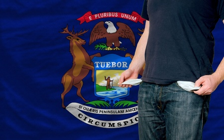 poor man showing empty pockets in front of american state of michigan flag Stock Photo
