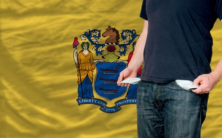poor man showing empty pockets in front of american state of new yersey flag Stock Photo - 12071174