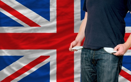 poor man showing empty pockets in front of uk flag