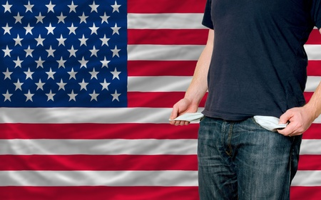 poor man showing empty pockets in front of us flag Stock Photo