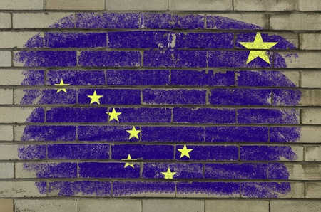 Chalky and grunge american state of alaska flag painted with color chalk on brick wall photo