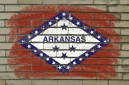 Chalky and grunge american state of arkansas flag painted with color chalk on brick wall photo