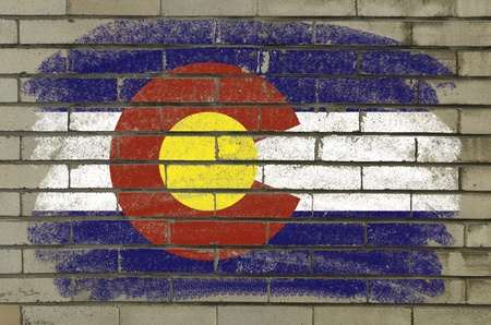 Chalky and grunge american state of colorado flag painted with color chalk on brick wall photo