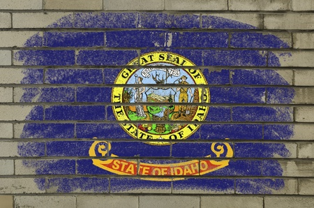 Chalky and grunge american state of idaho flag painted with color chalk on brick wall photo