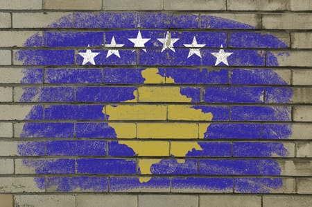 Chalky and grunge kosovo flag painted with color chalk on brick wall photo