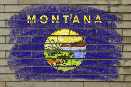 Chalky and grunge american state of montana flag painted with color chalk on brick wall photo