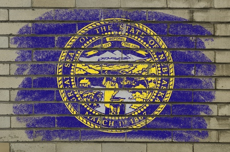 Chalky and grunge american state of nebraska flag painted with color chalk on brick wall photo