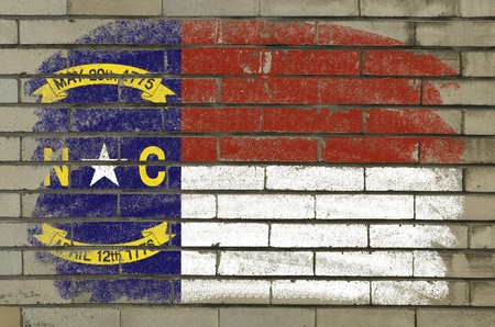 Chalky and grunge american state of north carolina flag painted with color chalk on brick wall photo