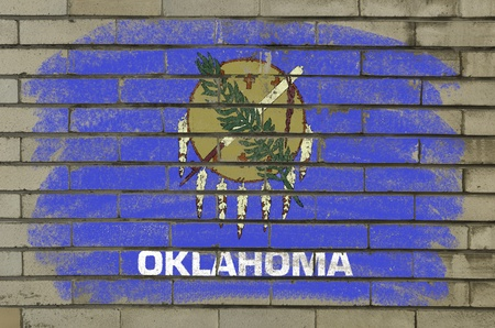Chalky and grunge american state of oklahoma flag painted with color chalk on brick wall photo