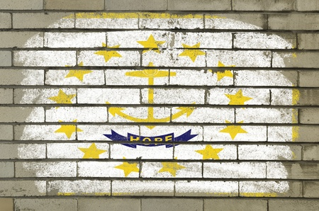 Chalky and grunge american state of rhode island flag painted with color chalk on brick wall photo