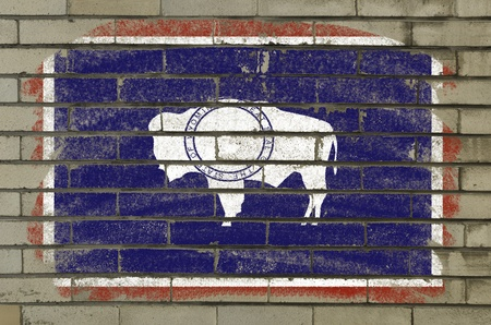 Chalky american state of wyoming flag painted with color chalk on brick wall photo