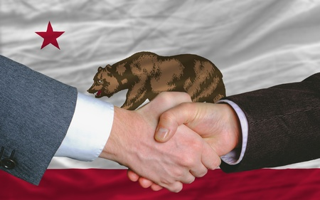 two businessmen shaking hands after good business investment  agreement in america, in front US state flag of california photo