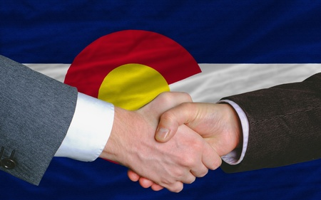 two businessmen shaking hands after good business investment  agreement in america, in front US state flag of colorado Stock Photo - 12172403
