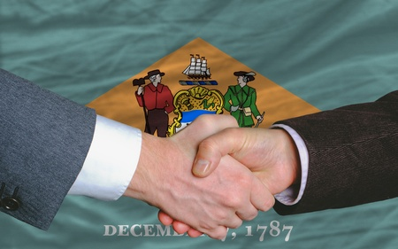 two businessmen shaking hands after good business investment  agreement in america, in front US state flag of delaware