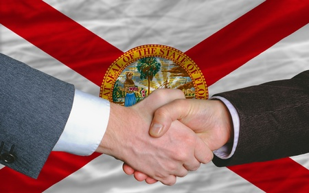 entrepeneur: two businessmen shaking hands after good business investment  agreement in america, in front US state flag of florida
