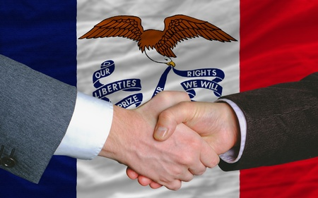 two businessmen shaking hands after good business investment  agreement in america, in front US state flag of iowa photo