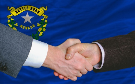 two businessmen shaking hands after good business investment agreement in front US state flag of nevada photo