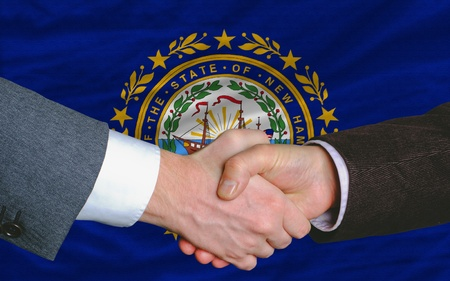 two businessmen shaking hands after good business investment agreement in front US state flag of new hampshire