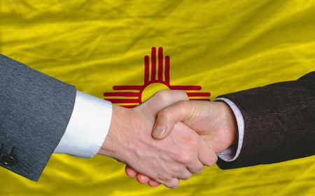 two businessmen shaking hands after good business investment agreement in front US state flag of new mexico Stock Photo - 12170457