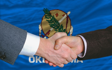 syndicate: two businessmen shaking hands after good business investment agreement in front US state flag of oklahoma