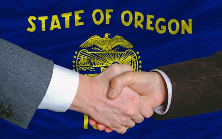entrepeneur: two businessmen shaking hands after good business investment agreement in front US state flag of oregon