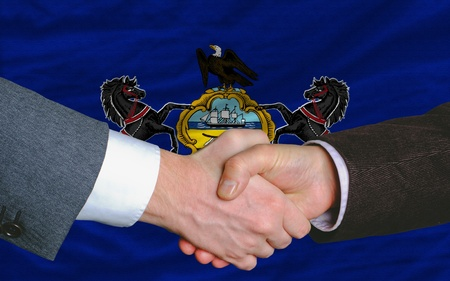 entrepeneur: two businessmen shaking hands after good business investment agreement in front US state flag of pennsylvania