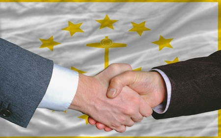 entrepeneur: two businessmen shaking hands after good business investment agreement in front US state flag of rhode island