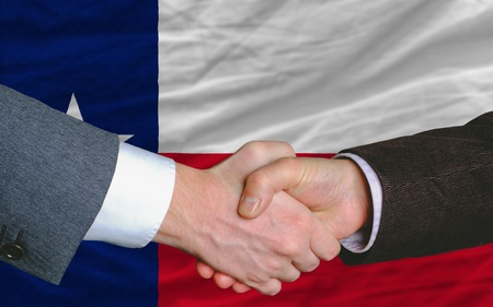 syndicate: two businessmen shaking hands after good business investment agreement in front US state flag of texas