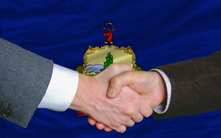 two businessmen shaking hands after good business investment agreement in front US state flag of vermont
