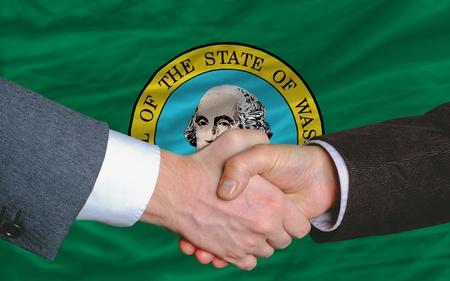 buen trato: delante de la bandera del estado norteamericano de Washington dos hombres de negocios apret�n de manos despu�s de mucho Foto de archivo