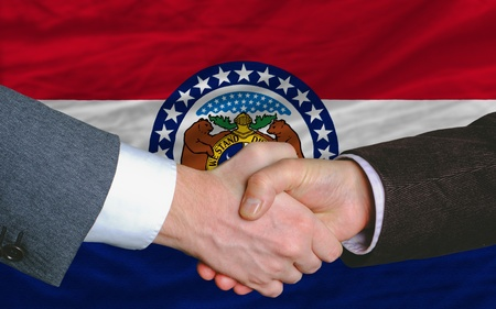 entrepeneur: two businessmen shaking hands after good business investment agreement in front US state flag of missouri