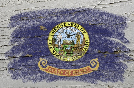 geography: Chalky american state of idaho flag precisely painted with color chalk on grunge wooden texture