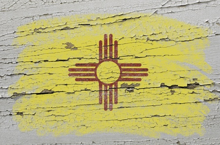Chalky american state of new mexico flag precisely painted with color chalk on grunge wooden texture photo