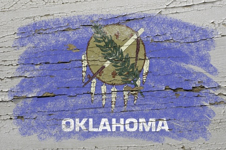 Chalky american state of oklahoma flag precisely painted with color chalk on grunge wooden texture Stock Photo